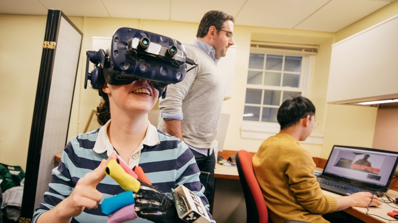 A student wears special gloves and a virtual reality headset while a student and professor watches her brainwaves on a computer monitor.